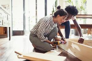 Two women constructing a shelf inside a home