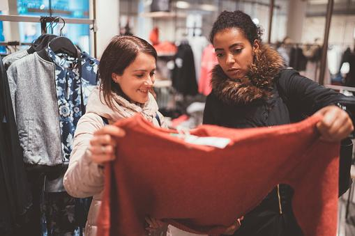Two women looking at the price of a sweater