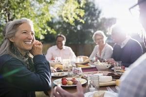 Group of older men and women enjoying a light dinner outside