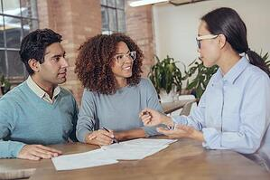 Young couple consulting with professional woman